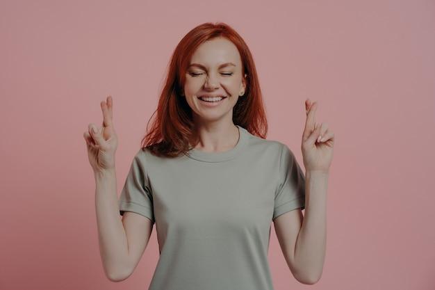 Студийный снимок обнадеживающей рыжеволосой студентки с закрытыми глазами в повседневной одежде, скрещивающей пальцы с суеверным выражением лица, просящей удачи перед экзаменом, изолированная на розовом фоне