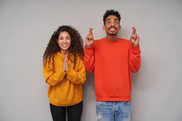 제기 손으로 회색 배경 위에 서서 널리 웃고있는 동안 모직 다채로운 스웨터와 청바지를 입고 매력적인 젊은 어두운 피부 곱슬 쌍을 바라는 스튜디오 샷