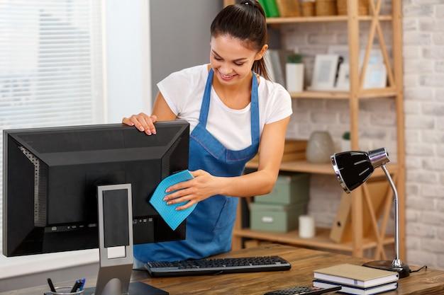 Студийный снимок домработницы. красивая женщина, чистящая компьютер в офисе и улыбается