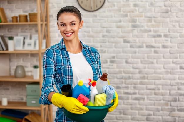 ハウスキーパーのスタジオショット。美しい女性の掃除室。手袋を着用し、笑顔で消毒剤入りのボトルでいっぱいのボウルを保持している女性