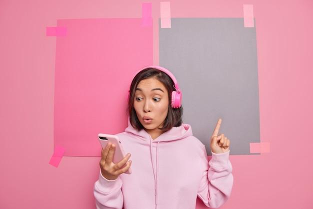 Студийный снимок впечатленной азиатской девушки показывает место для рекламы, смотрит на дисплей смартфона, слушает звуковую дорожку, показывает продвижение, одетую в повседневную толстовку с капюшоном, изолированную на розовой стене.