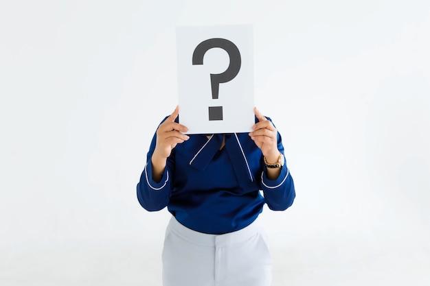 비즈니스 정장을 입은 미확인된 식별할 수 없는 얼굴 없는 여성 직원의 스튜디오 샷은 배경에 대한 답을 생각하는 물음표 종이 판지 표지 덮개 얼굴을 들고 있습니다.