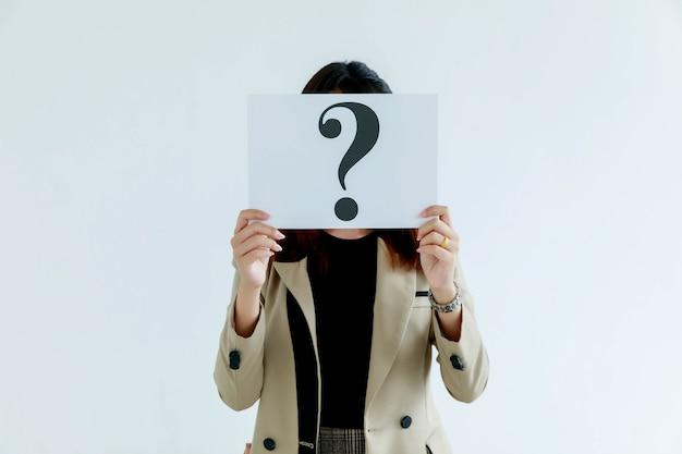 비즈니스 정장을 입은 익명의 식별할 수 없는 얼굴 없는 여성 직원의 스튜디오 샷은 배경에 대한 답변을 생각하는 물음표 종이 판지 표지 얼굴을 들고 있습니다.