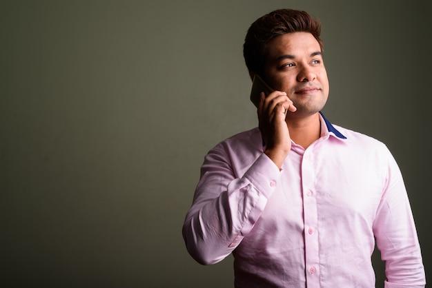 色付きの背景にピンクのシャツを着ているインドのビジネスマンのスタジオ撮影