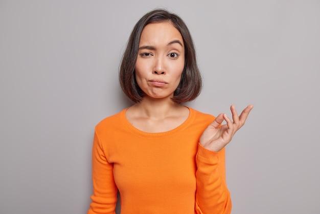 분개한 아시아 여성의 스튜디오 샷은 회색 스튜디오 벽에 기대어 캐주얼한 오렌지색 점퍼 포즈를 취한 채 결정을 내릴 수 없다는 것을 머뭇거리며 손바닥을 들어올린다.