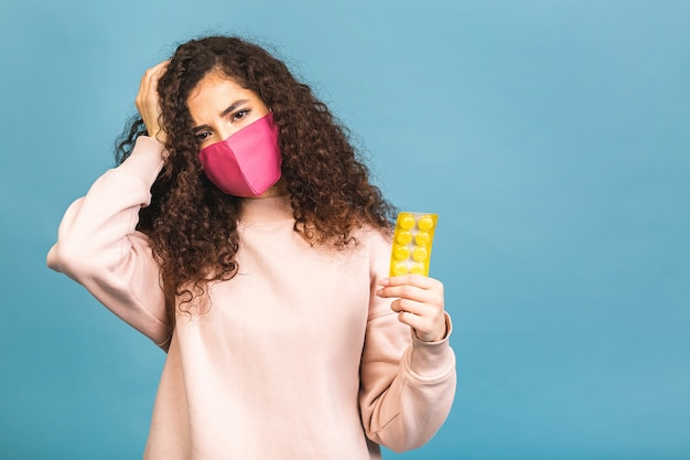 Студийный снимок инфицированной женщины с таблетками в руках, дамы в защитной маске, предотвращающей распространение опасного вируса