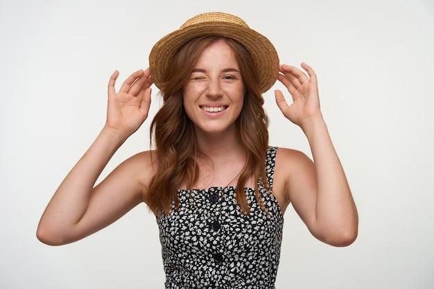 白い背景の上に立っている赤いウェーブのかかった髪、彼女の頭にカンカン帽の帽子を保持するために手を上げて、カメラでウィンクし、前向きに笑っているうれしそうなかわいい若い女性のスタジオショット
