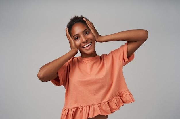 그녀의 머리에 손바닥을 들고 회색 벽 위에 서있는 동안 앞에 행복하게 웃는 즐거운 젊은 사랑스러운 갈색 머리 곱슬 아가씨의 스튜디오 샷