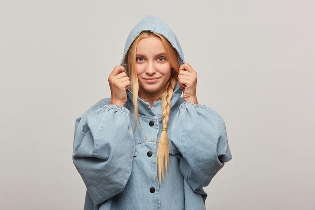 三つ編みで素敵な美しいブロンドの女性のスタジオショット、手はフードを保ち、幸せな優しく微笑む