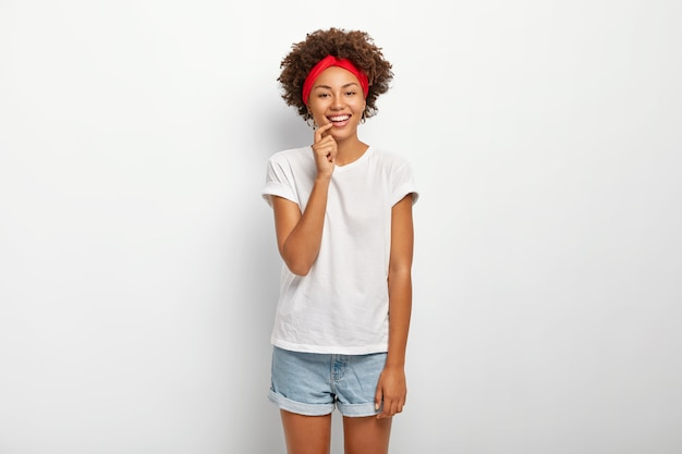 사랑스러운 곱슬 머리 여자의 스튜디오 샷은 즐거운 순간을 즐기고, 부드럽게 미소 짓고, 빨간 머리띠, 캐주얼 티셔츠와 데님 반바지를 입고 흰색 배경에 고립 된