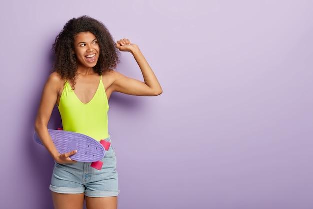 素敵な巻き毛の女性がスケートボードでポーズをとるスタジオショット、アクティブなライドの後に休憩を取る、黒い肌