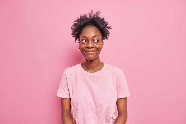 사랑스러운 어두운 피부의 여성의 스튜디오 샷은 행복한 만족스러운 표정으로 시선을 돌리며 곱슬머리를 하고 있습니다.