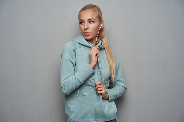 ヘッドフォンで音楽を聴き、真面目な顔で脇を見て、ライトグレーの背景の上に運動着を着たポニーテールの髪型の素敵な若いスポーティなブロンドの女性のスタジオショット