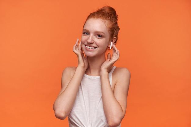 オレンジ色の背景の上に立っている間ヘッドフォンで音楽を聴いて、ポジティブで魅力的な笑顔でカメラを見ているセクシーなパンの髪型を持つ素敵な若い女性のスタジオショット