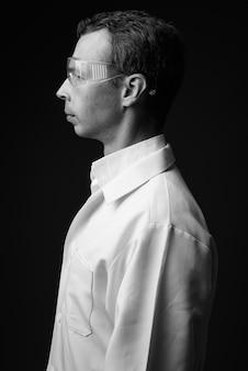 黒と白の灰色の壁に保護メガネをかけている男性医師のスタジオショット