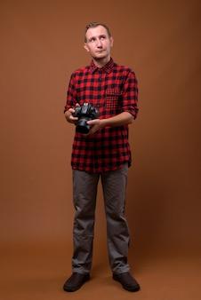 Студийный снимок человека на коричневом