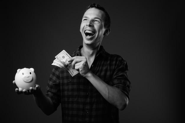 黒と白の灰色の壁に市松模様のシャツを着ている男のスタジオショット