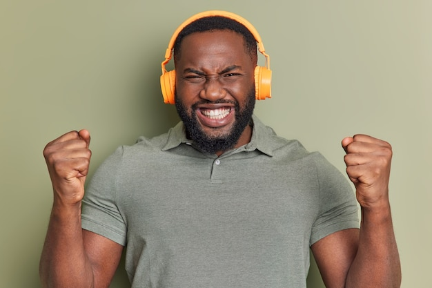 太いあごひげを生やした男のスタジオショットは、食いしばりを上げますか?拳は成功を祝う勝者はステレオヘッドフォンを着用し、屋内で音楽のポーズを聞くように感じます