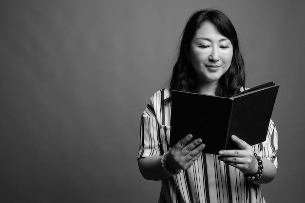 흑인과 백인 회색에 대한 성숙한 아름다운 일본 여자의 스튜디오 샷