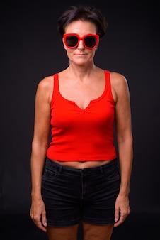 黒の背景に短い髪の成熟した美しいスカンジナビアの女性のスタジオショット