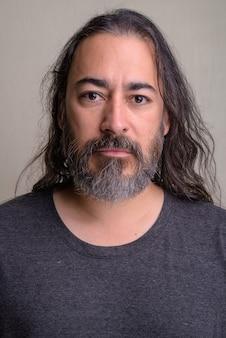 Студийный снимок зрелого красивого бородатого многонационального мужчины с длинными волосами