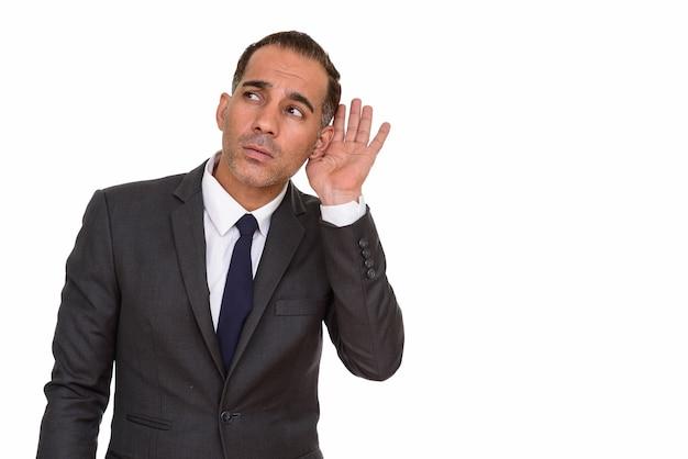 Студийный снимок зрелого красивого персидского бизнесмена в костюме, изолированном на белом фоне