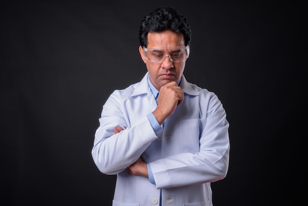 Студийный снимок зрелого индийского врача-мужчины на черном фоне