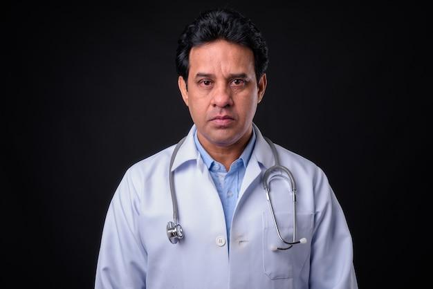 黒の背景に成熟したインド人医師のスタジオショット