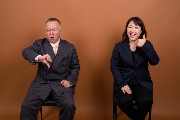 成熟した日本のビジネスマンと茶色の背景に対して一緒に成熟した日本の実業家のスタジオ撮影