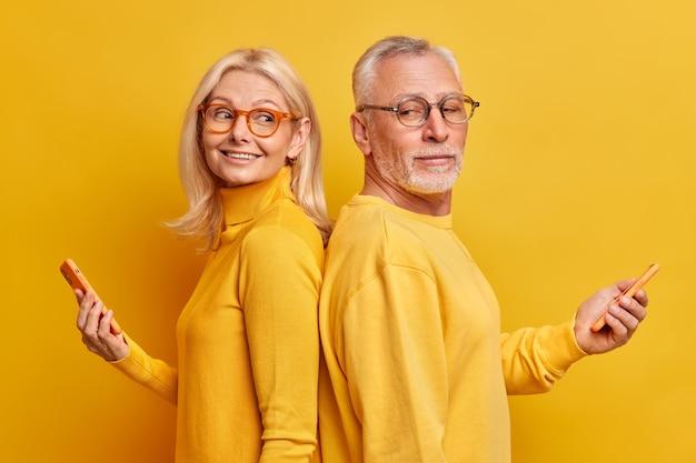 成熟した男性と女性のモデルのスタジオショットは、黄色の壁に隔離されたソーシャルネットワークでインターネットチャットをサーフィンする現代のガジェットを手に持って互いに立ち向かいます