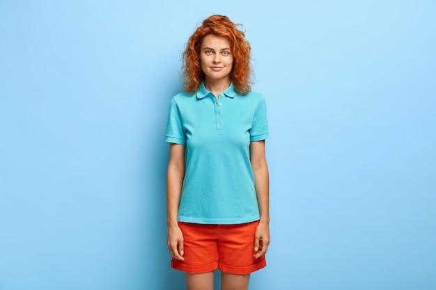 파란색 벽에 포즈 물결 모양의 빨간 머리를 가진 밀레 니얼 여자의 스튜디오 샷