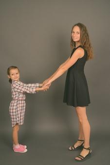 회색 벽에 함께 결합 어머니와 딸의 스튜디오 샷