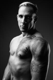 黒と白で上半身裸の筋肉質の男のスタジオショット