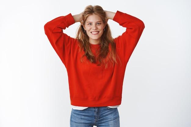 귀여운 주근깨가 있는 낙천적이고 매력적인 젊은 여성의 스튜디오 샷은 큰 빨간 스웨터를 입고 평온한 냉정한 포즈로 머리 뒤쪽에 손을 잡고 있는 멋진 하얀 미소로 즐겁게 웃고 있습니다.
