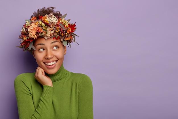 낙관적 인 꿈꾸는 아가씨의 스튜디오 샷은 시선을 제쳐두고 뺨을 만지며 머리 주위에 가을 자연 화환을 착용합니다.