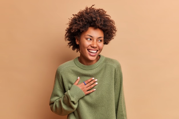 大喜びの女性のスタジオショットは、面白い話が胸に手を保ち、ベージュの壁に隔離されたカジュアルなジャンパーに広く身を包んだ右の笑顔を見ると大声で笑います