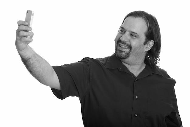 Студийный снимок полного бородатого мужчины, изолированного на белом фоне в черно-белом
