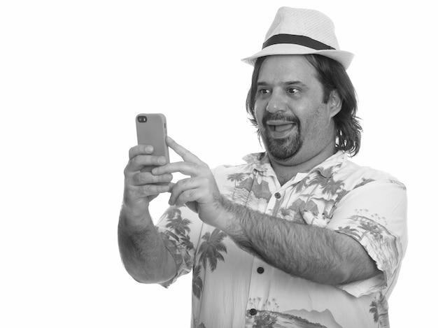 Студийный снимок бородатого туриста с избыточным весом, готового к отпуску, изолированного на белом фоне в черно-белом