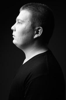 Студийный снимок полного молодого человека у черной стены в черно-белом