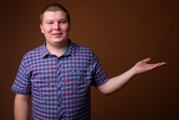 茶色の背景に紫色の市松模様のシャツを着ている太りすぎの若い男のスタジオショット
