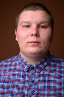 갈색 배경에 보라색 체크 무늬 셔츠를 입고 과체중 젊은 남자의 스튜디오 샷