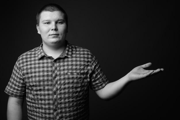 灰色の壁に紫色の市松模様のシャツを着ている太りすぎの若い男のスタジオショット