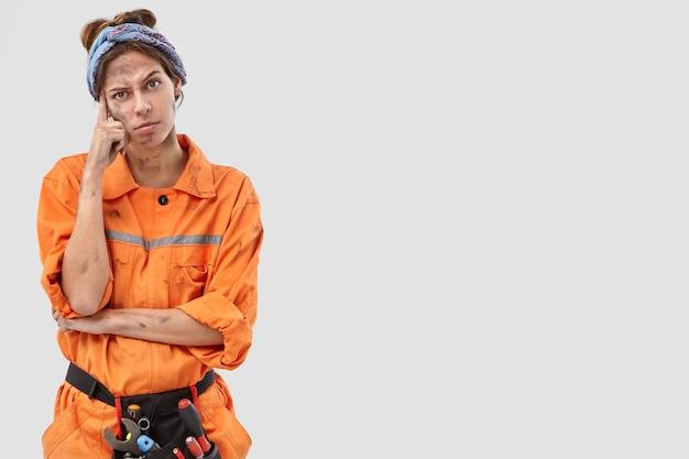 Студийный снимок задумчивой работницы, позирующей у белой стены