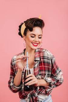 ピンクの背景に分離されたピンナップ女性のスタジオショット。ソーダを飲む市松模様のシャツで笑っている女の子。