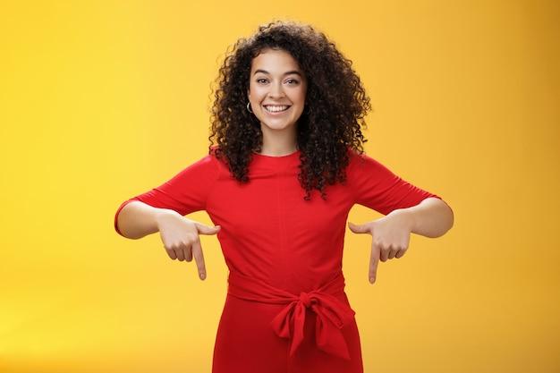 Студийный снимок приятной улыбающейся молодой кудрявой женщины в красном платье, указывающей вниз указательными пальцами, которая рекламирует потрясающее мероприятие, широко улыбаясь, предлагая попробовать или купить через желтую стену.