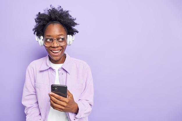 Студийный снимок довольной афроамериканской женщины, которая наслаждается любимым аудио-плейлистом, слушает музыку в смартфоне и наушниках