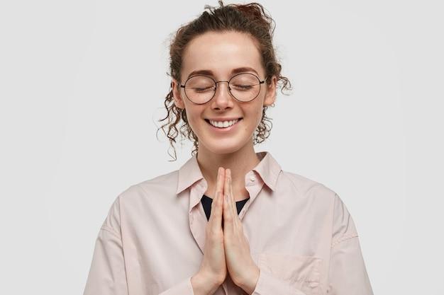 Студийный снимок довольного веснушчатого подростка в очках, позирующего на фоне белой стены