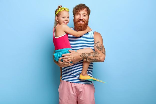 Студийный снимок довольных имбирных отца и дочери, позирующих в нарядах для бассейна