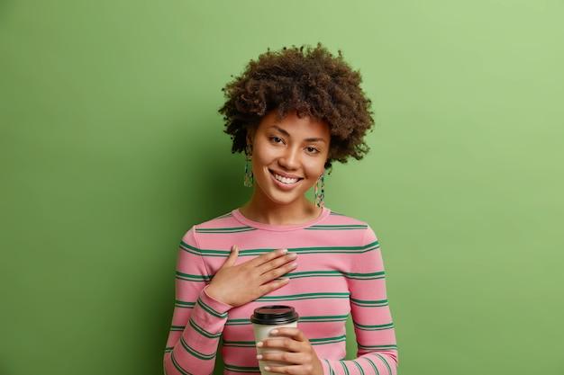 Студийный снимок довольной благодарной женщины, держащей руку на груди, слышит душевные слова, держит одноразовую чашку кофе наклоняет голову в полосатом джемпере, изолированном над яркой зеленой стеной