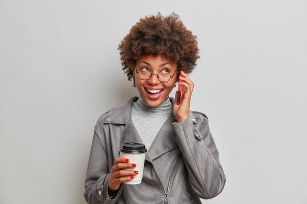 긍정적 인 사랑스러운 젊은 아프리카 계 미국인 womanhas의 스튜디오 샷 즐거운 대화는 회색 벽 위에 고립 된 귀 음료 테이크 아웃 커피 근처에 스마트 폰을 유지합니다.